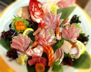 creative sashimi with gold fish in a big plate